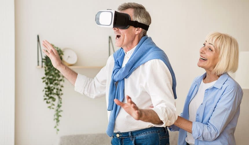 New feelings. Excited mature man using the VR glasses, wife standing behind husband